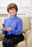 Mulher que senta-se no envio de mensagem de texto do sofá Foto de Stock Royalty Free