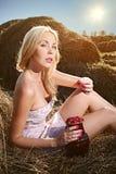 A mulher que senta-se no feno e come framboesas Fotos de Stock Royalty Free