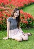 Mulher que senta-se no jardim do verão Imagem de Stock