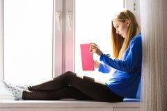 Mulher que senta-se no livro de leitura do peitoril da janela em casa imagens de stock royalty free