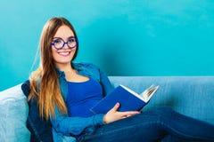 Mulher que senta-se no livro de leitura do sofá em casa Fotografia de Stock Royalty Free