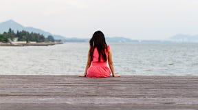Mulher que senta-se no molhe de madeira imagem de stock royalty free
