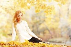 Mulher que senta-se no parque do outono Fotos de Stock Royalty Free