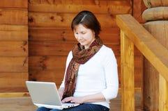 Mulher que senta-se no patamar de madeira Imagens de Stock Royalty Free