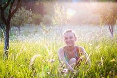 Mulher que senta-se no prado Imagens de Stock