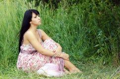 Mulher que senta-se no prado do verão imagens de stock