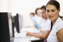 Mulher que senta-se no quarto de computador com povos Fotografia de Stock Royalty Free