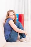 Mulher que senta-se no sentimento do sofá confortável e no sorriso imagens de stock