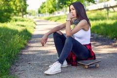 Mulher que senta-se no skate Fora, estilo de vida urbano foto de stock