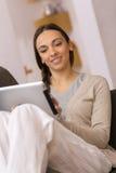 Mulher que senta-se no sofá com PC da tabuleta Fotos de Stock