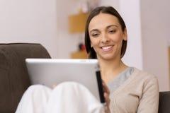 Mulher que senta-se no sofá com PC da tabuleta Fotografia de Stock Royalty Free