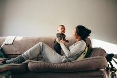 Mulher que senta-se no sofá com seu bebê imagem de stock royalty free