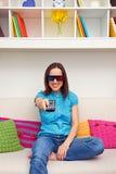 Mulher que senta-se no sofá e no filme 3d de observação Foto de Stock