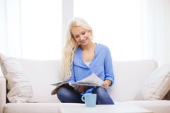 Mulher que senta-se no sofá e que lê o compartimento Foto de Stock