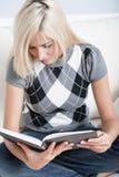 Mulher que senta-se no sofá e que lê um livro fotos de stock royalty free