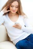 Mulher que senta-se no sofá e que olha seu telefone Imagens de Stock Royalty Free