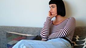 Mulher que senta-se no sofá em casa vídeos de arquivo