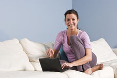 Mulher que senta-se no sofá em casa com portátil Fotos de Stock
