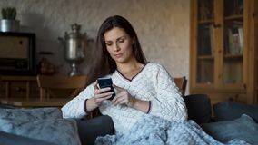 A mulher que senta-se no sofá envolveu em uma cobertura e em texting no telefone filme
