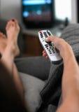 Mulher que senta-se no sofá para mudar as canaletas em y Foto de Stock Royalty Free