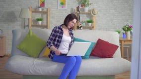 A mulher que senta-se no sofá que trabalha em um portátil está experimentando a dor e o incômodo das hemorroidas vídeos de arquivo