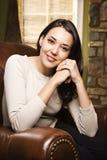 Mulher que senta-se no sorriso da cadeira Imagem de Stock
