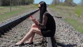 Mulher que senta-se no telefone esperto railway e usando-se video estoque