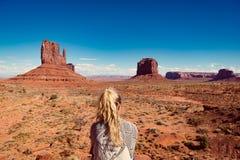 A mulher que senta-se no vale do monumento com vermelho balança a vista geral Foto de Stock