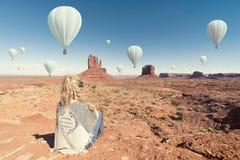 Mulher que senta-se no vale do monumento com vista geral quente dos ballons Imagens de Stock Royalty Free