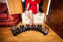 Mulher que senta-se no vestuário e que olha a fileira das sapatas Fotos de Stock