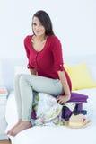Mulher que senta-se para baixo sobre sua mala de viagem Imagens de Stock Royalty Free