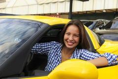Mulher que senta-se para dentro de seu carro de esportes novo Fotografia de Stock