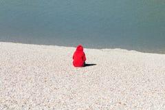 Mulher que senta-se pela água no hoodie vermelho Imagens de Stock