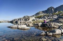 Mulher que senta-se pelo lago imóvel mountain Imagens de Stock Royalty Free