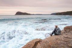 Mulher que senta-se pelo oceano que deixa ondas dobrar em seus pés fotografia de stock royalty free