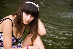 Mulher que senta-se perto da água Fotografia de Stock Royalty Free