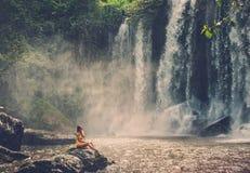 Mulher que senta-se perto da cachoeira que aprecia o sol, Phnom Koulen em Siem Reap, Camboja Imagens de Stock Royalty Free