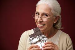 Mulher que senta-se sobre a obscuridade - fundo azul que come o chocolate fotografia de stock