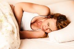 Mulher que sente doente com a dor de estômago na cama - cause dor no estômago Foto de Stock