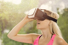 Mulher que sente entusiasmado para usar auriculares da realidade virtual fotografia de stock