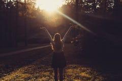 Mulher que sente livre no por do sol Silhueta dos braços de espalhamento da mulher com seus polegares acima, estando na floresta  Imagem de Stock