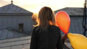 Mulher que sente o passeio feliz com o balão no telhado Vista traseira filme