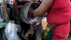 Mulher que shredding o coco com barbeador motorizado supostamente um trabalho típico do ` s do homem aumentar o salário da famíli vídeos de arquivo