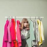 Mulher que sneaking entre a roupa na alameda ou no vestuário Imagem de Stock