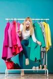 Mulher que sneaking entre a roupa na alameda ou no vestuário Imagem de Stock Royalty Free