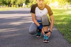 Mulher que sofre da dor em ferimento de pé após movimentar-se de corrida do exercício do esporte e no exercício exterior no parqu imagem de stock royalty free