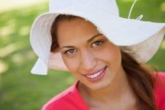 Mulher que sorri ao desgastar um chapéu branco fotografia de stock royalty free