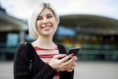 Mulher que sorri ao usar o telefone celular fora do estação de caminhos-de-ferro fotografia de stock