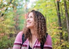 Mulher que sorri e que caminha através da floresta no outono, cabelo encaracolado Foto de Stock