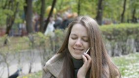 Mulher que sorri e que fala no telefone celular no parque da cidade filme